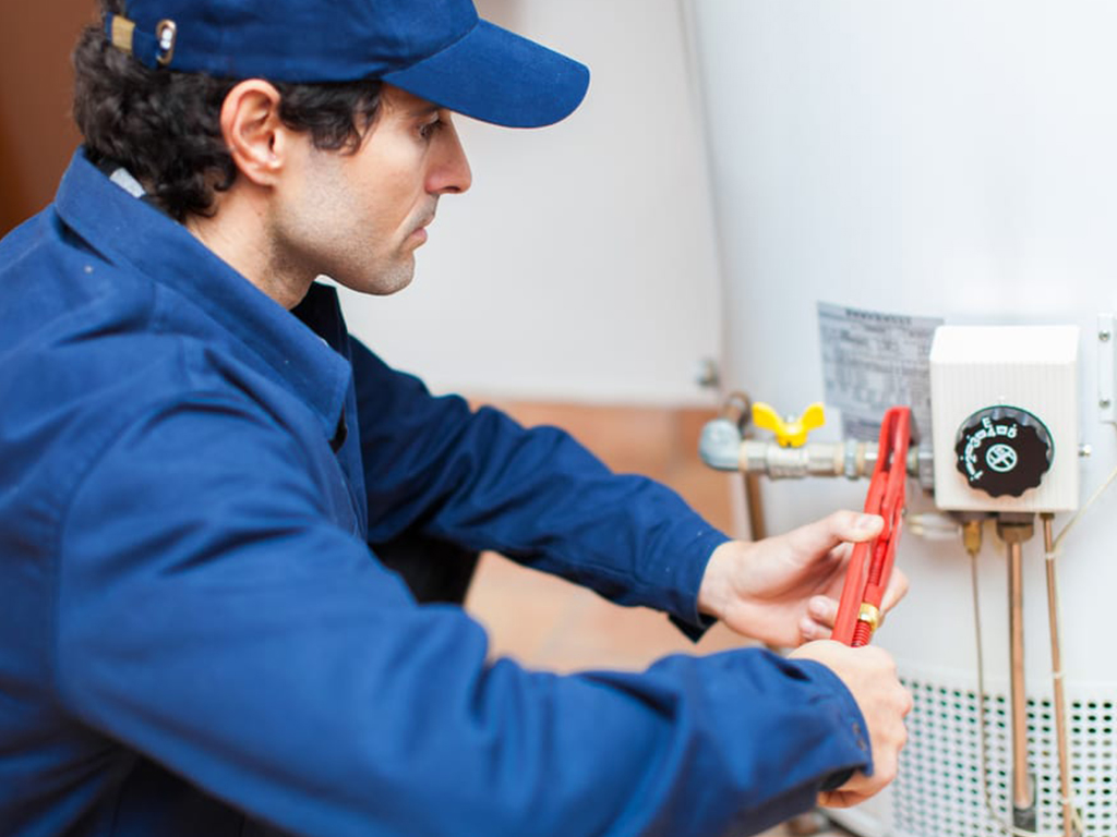 An image of a plumber installing a new water heater.